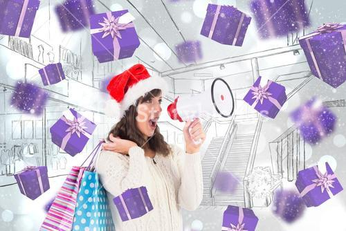 Composite image of festive brunette holding megaphone and bags