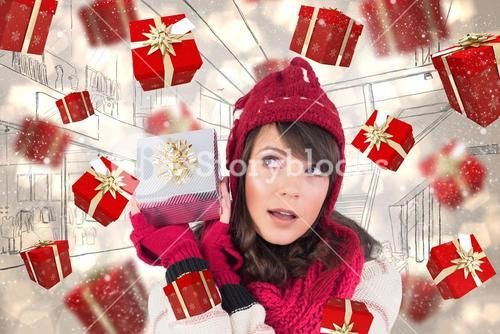 Composite image of young woman shaking her gift in order to guess what it is