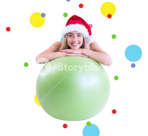 Composite image of festive fit blonde posing with exercise ball
