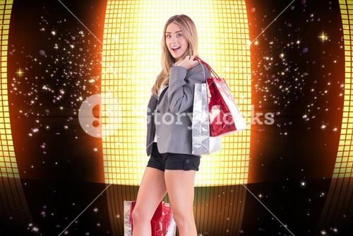 Composite image of stylish blonde holding shopping bags