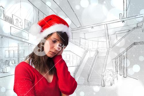 Composite image of sad woman in santa hat holding her head