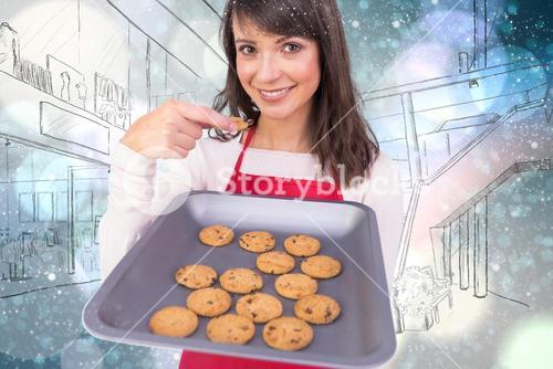 Composite image of festive brunette showing hot cookies