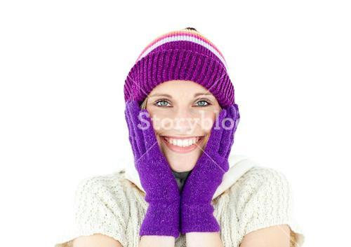 Positive woman with a colorful hat and a pullover smiling at the camera
