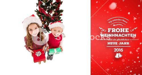 Composite image of festive little siblings smiling at camera holding gifts