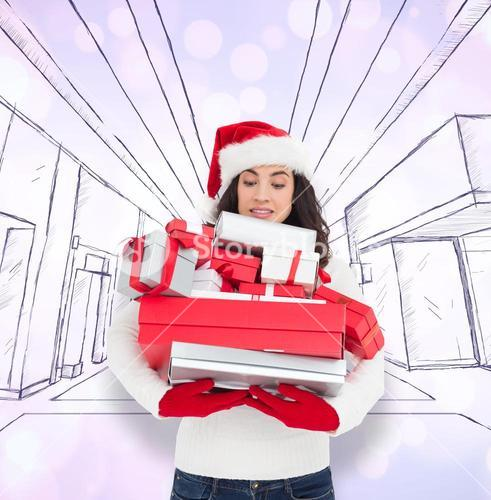 Composite image of stressed brunette in santa hat holding pile of gifts