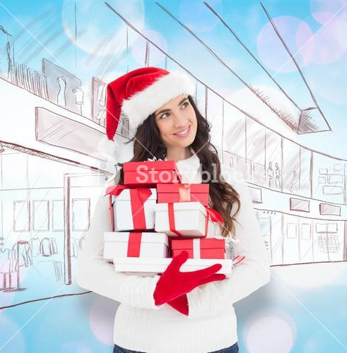 Composite image of joyful brunette in santa hat and red gloves holding pile of gifts