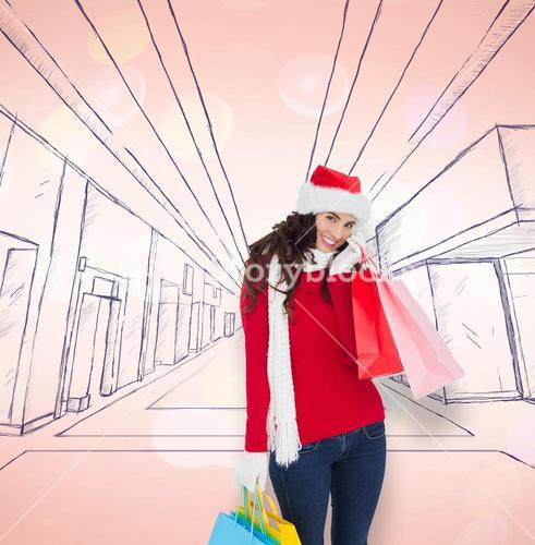 Composite image of happy brunette in winter wear holding shopping bags