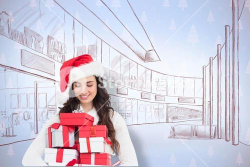 Composite image of festive brunette holding pile of gifts
