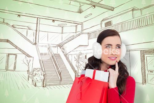 Composite image of brunette with ear muffs holding shopping bag full of gifts