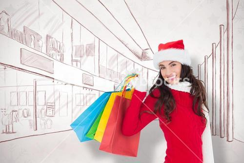 Composite image of festive brunette in winter wear holding shopping bags