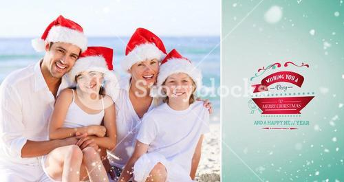 Composite image of family during christmas day at the beach