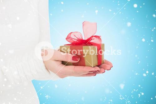 Composite image of pretty woman holding gild gift