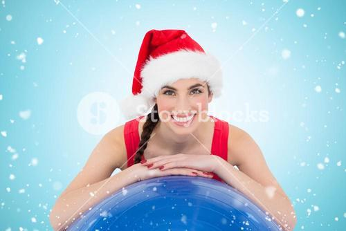 Composite image of festive fit brunette leaning on exercise ball