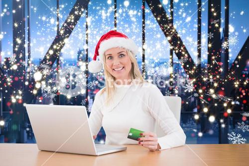 Composite image of festive blonde shopping online