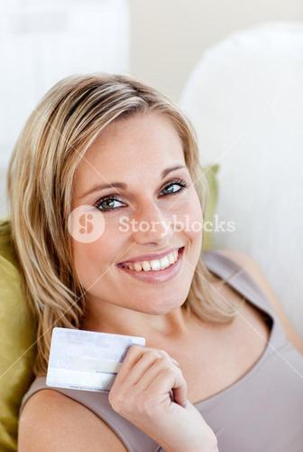 Cheerful woman holding a card sitting on a sofa in the livingroom