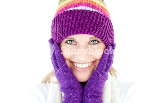 Radiant young woman with cap and gloves in the winter smiling at the camera