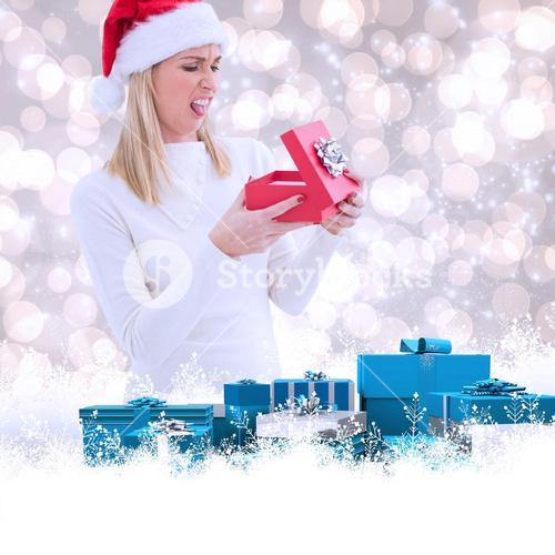 Composite image of disappointed blonde opening christmas gift