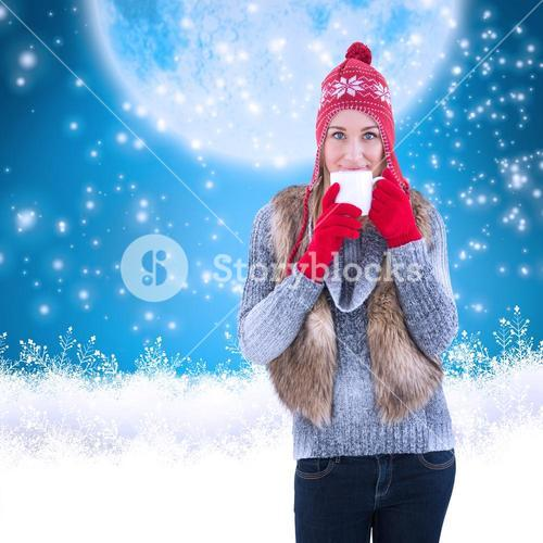 Composite image of woman in winter clothes holding a mug