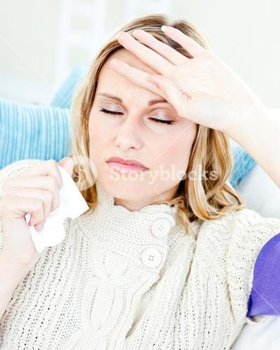 Diseased woman with headache lying on the sofa in the livingroom at home