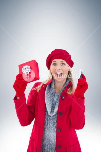 Festive blonde holding gift and credit card