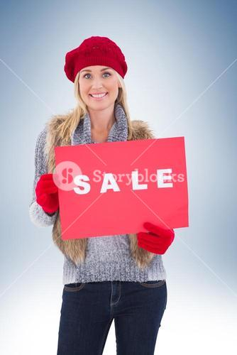 Blonde in winter clothes holding sale sign