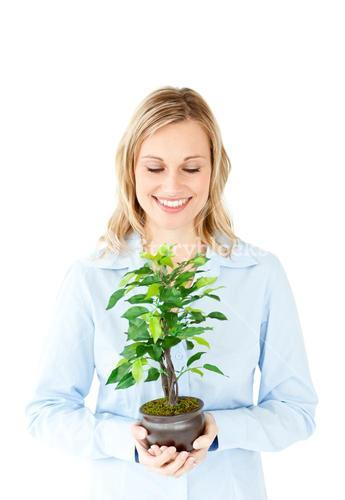 Portrait of a charismatic businesswoman holding a plant