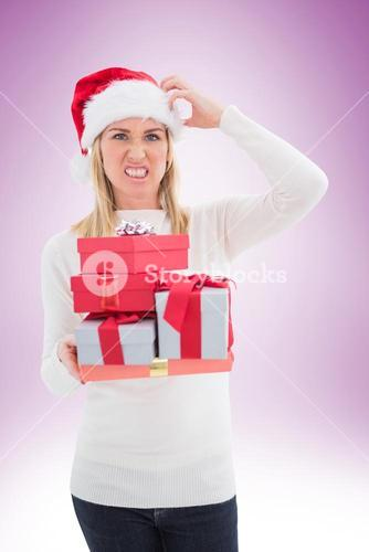 Stressed blonde in santa hat holding gifts