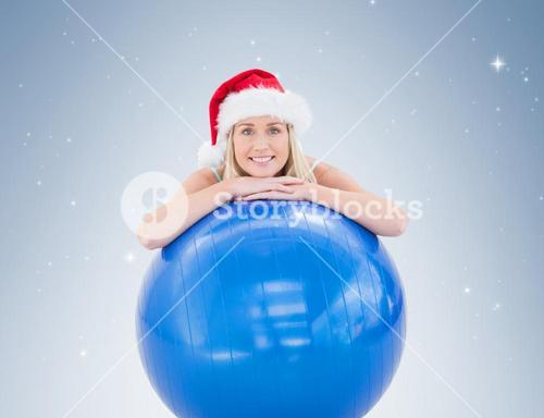 Festive fit blonde leaning on exercise ball