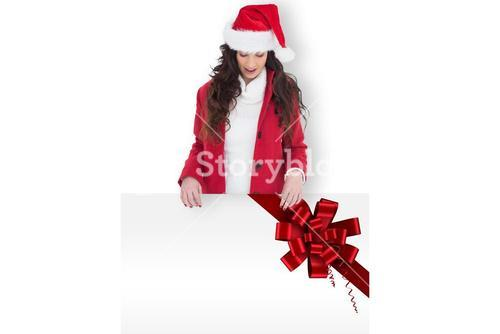 Composite image of festive brunette showing white poster