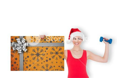 Composite image of festive fit brunette holding gift card and dumbbell