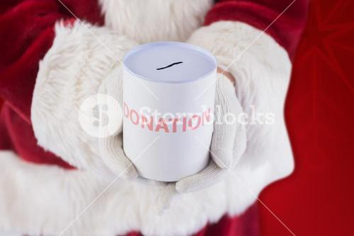 Composite image of santa holds a can for donations