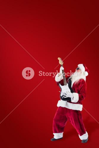 Composite image of santa playing electric guitar