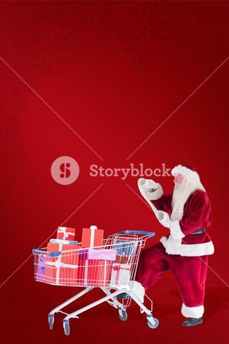 Composite image of santa pushes a shopping cart while reading
