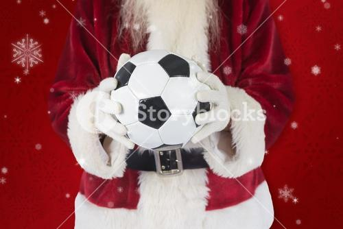 Composite image of santa holds a classic football