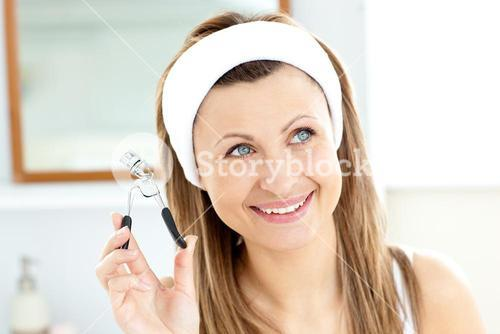 Smiling woman holding an eyelash curler looking at the camera in the bathroom
