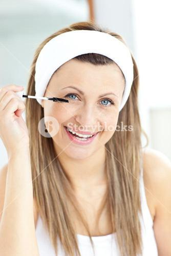 Glad young woman using mascara in the bathroom