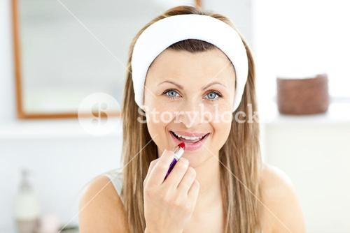 Delighted young woman using a red lipstick in the bathroom