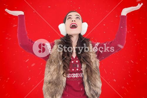 Composite image of brunette in winter clothes with hands out