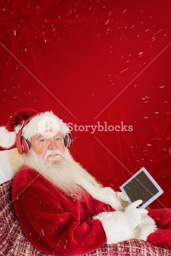 Composite image of father christmas listening to music with tablet