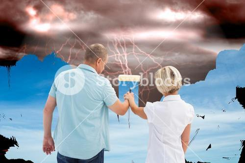 Composite image of happy older couple painting