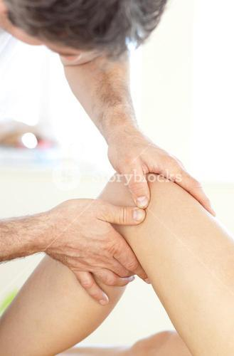 Close up of a young physical therapist giving a leg massage