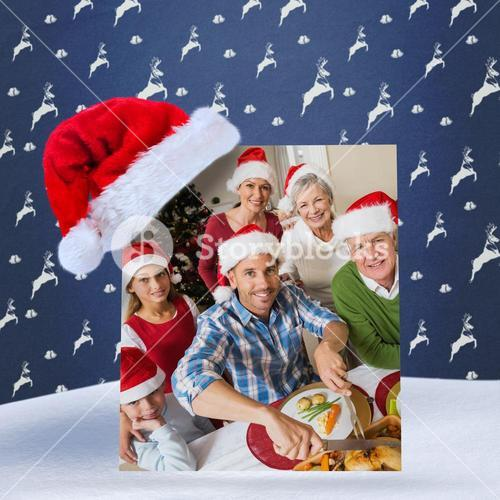 Composite image of father in santa hat carving chicken at christmas dinner