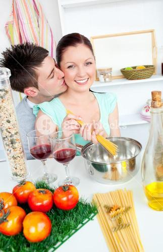 Bright couple preparing spaghetti in the kitchen and drinkng wine