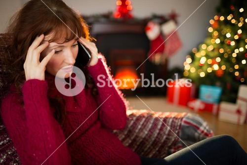 Concentrated redhead on the phone at christmas