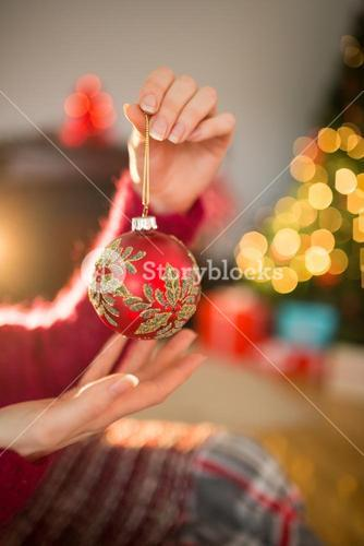 Woman in jumper holding red bauble at christmas