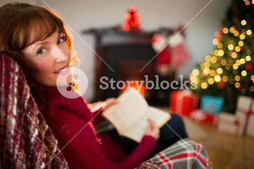 Happy redhead reading a book at christmas