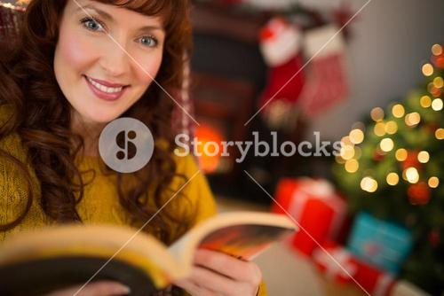 Peaceful redhead reading a book at christmas