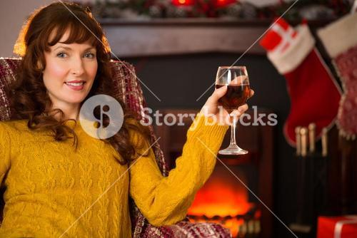 Woman sitting on a couch while holding a glass of red wine