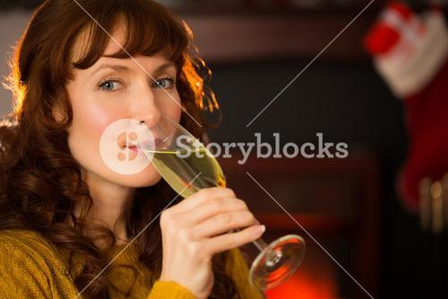 Pretty redhead drinking glass of champagne on couch
