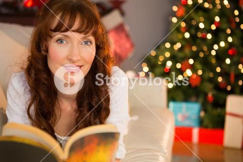 Pretty woman lying on a cosy couch reading book